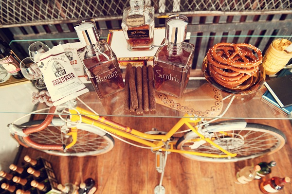 Whiskey table at wedding with old bike holding it up.
