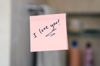 I love you written on a post-it note attached to a mirror.
