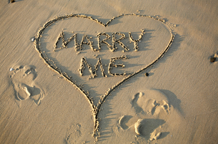 Marry me written in the sand with heart around it.