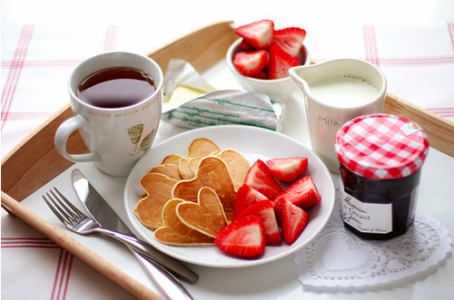 Tray with coffee, butter, strawberries, milk, jam and heart shaped pancakes.