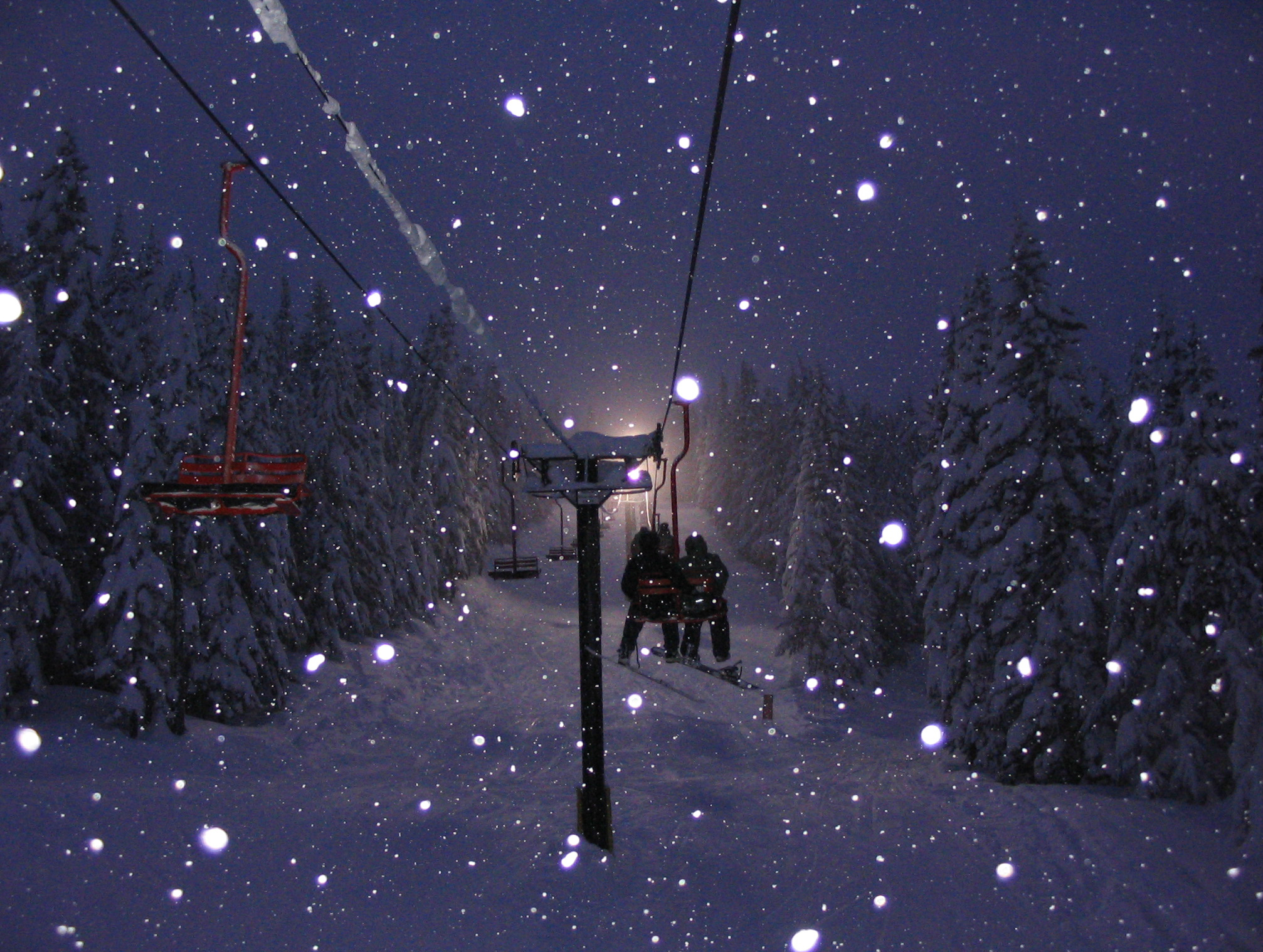 Couple on chairlift with snow falling on the mountain.