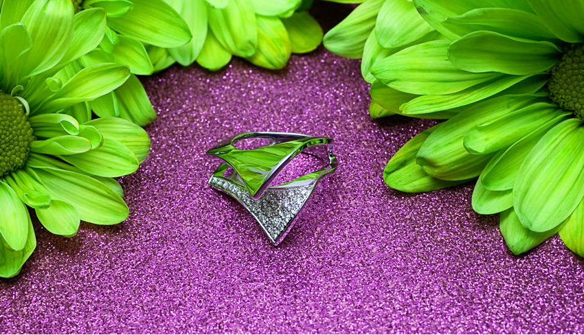 White gold engagement ring on purple sand next to green flowers.