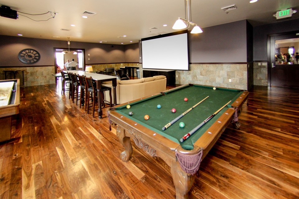 Groom room with bar, projector screen and pool tables.