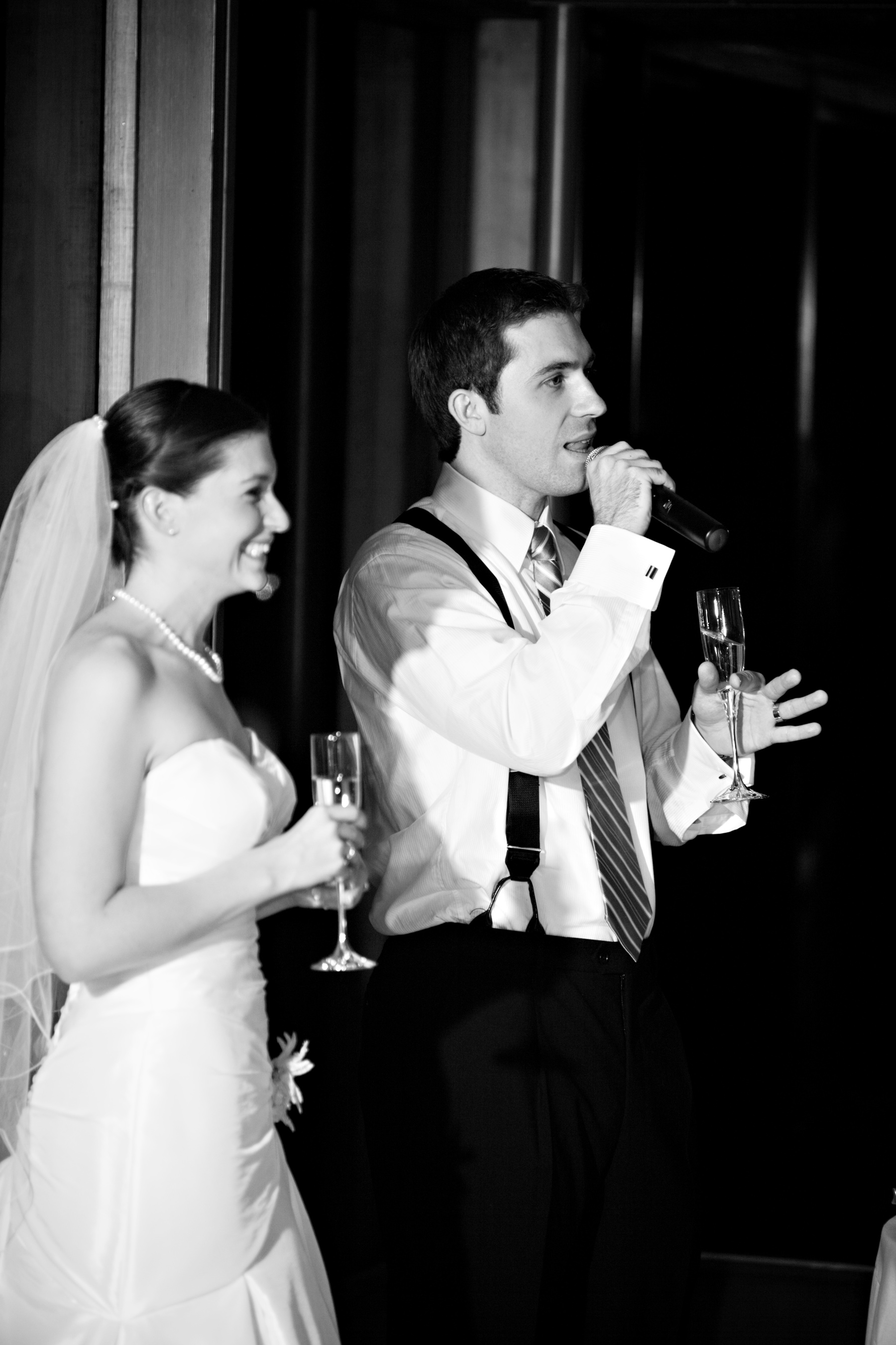 Groom giving wedding speech standing next to his bride.