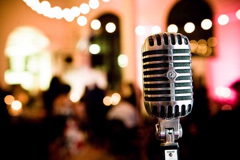 Old fashioned microphone with wedding reception in the background.