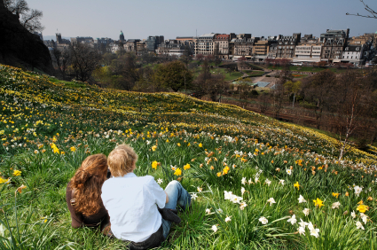 Man and women sitting in grass looking at city.
