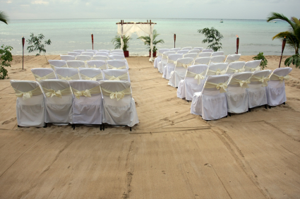 White chairs setup on beach for tropical wedding ceremony.