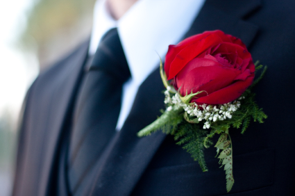 Groom in black suit with red rose boutonniere on his wedding day.