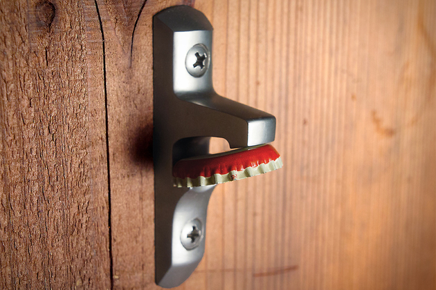 A bottle opener attached to a wall that holds caps using a magnet.