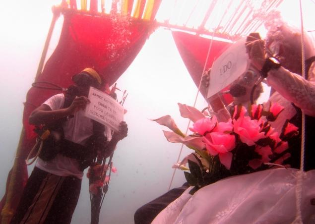 Bride and groom underwater in scuba gear saying