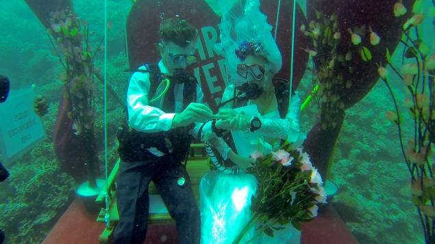 Bride and groom underwater in scuba gear exchanging rings.