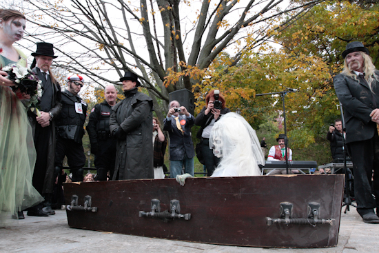 Zombie bride getting out of coffin during wedding ceremony.